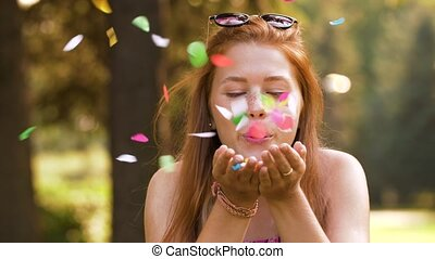 teenage girl blowing confetti off hands in park - people and...