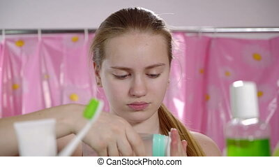 Teenage girl cleaning face skin applying skincare cleanser for teens in bathroom