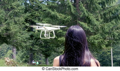 Teenage girl controlling drone with remote control in summer...
