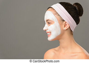Teenage girl cosmetics mask beauty looking away on gray...