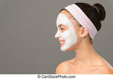 Teenage girl cosmetics mask beauty looking away on gray...