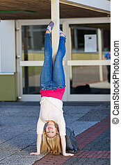 Teenage girl doing handstands at school - Pretty young blond...