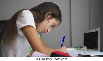 Teenage girl doing homework for school in her room, on the desk