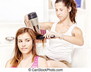 Teenage girl dries hair to her friends
