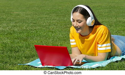 Teenage girl e learning with a laptop on the grass - Happy...