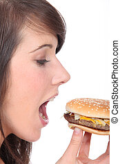 teenage girl eating an hamburger