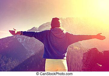 Teenage girl feel freedom in mountains scenery.