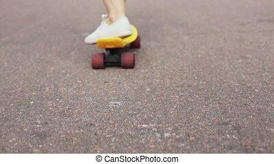 teenage girl feet riding short modern skateboard -...