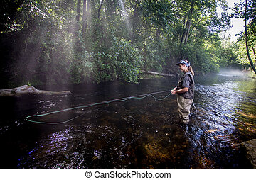Teenage Girl fly fishing on a small river in summer time.