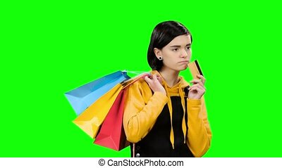 Teenage girl goes shopping with packages and a credit card in hand. Green screen