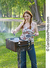 Teenage Girl Grilling Hamburgers at a Park