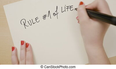 Teenage girl hands writing rule hashtag one of life do what...