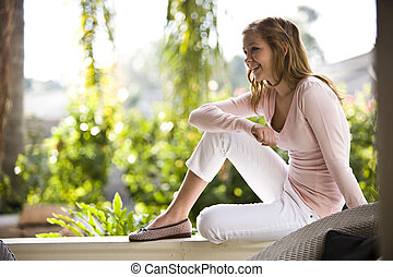 Happy teenage girl relaxing on terrace railing