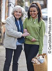 Teenage Girl Helping Senior Woman Carry Shopping