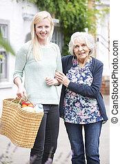 Teenage Girl Helping Senior Woman To Carry Shopping