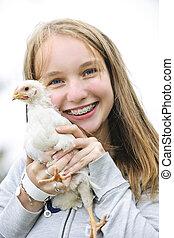 Teenage girl holding chicken