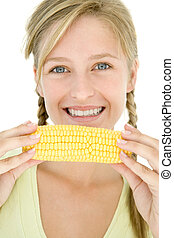 Teenage girl holding corn on cob and smiling
