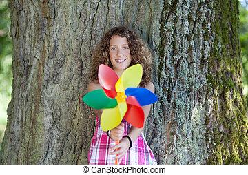 Teenage Girl Holding Pinwheel While Leaning On Tree Trunk