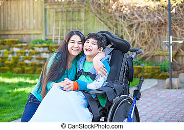 Teenage girl hugging disabled brother in wheelchair outdoors