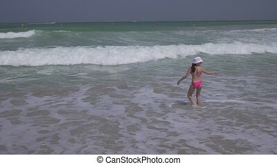 Teenage girl in a bathing suit happily jumps in the waves of Persian Gulf on beach of Dubai