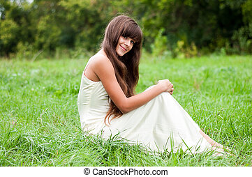 Teenage girl in a white dress on the nature