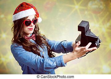 Teenage girl in Christmas hat making selfi with retro camera...