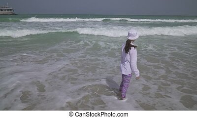 Teenage girl in clothes joyfully jumping in the waves of Persian Gulf on the beach of Dubai