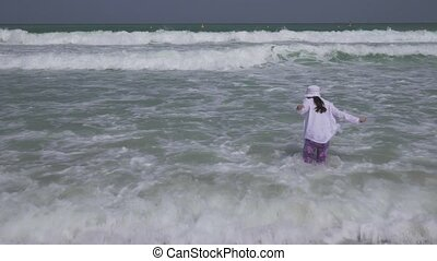 Teenage girl in a bathing suit happily jumps in the waves of persian