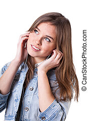 Teenage girl in denim jacket listening to music with ...