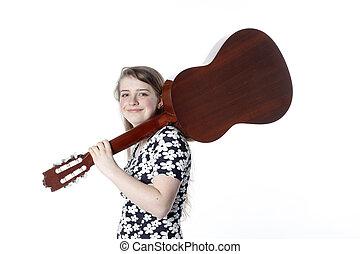 teenage girl in dress holds guitar on shoulder in studio