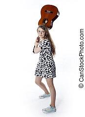 teenage girl in dress swings guitar in studio