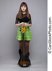 Teenage girl in dress with guitar