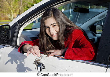 Teenage girl in driver's seat holding keys