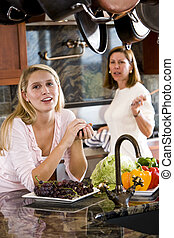 Teenage girl in kitchen chatting with mother