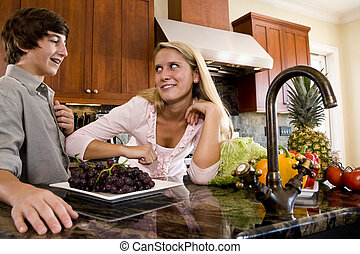 Teenage girl in kitchen talking with younger brother