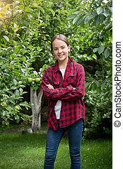 Teenage girl in red checkered shirt posing at apple garden
