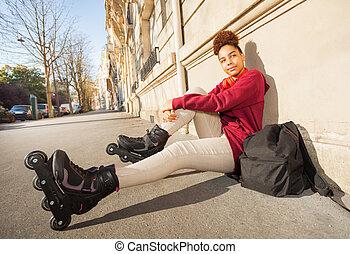Teenage girl in rollerblades sitting at sidewalk