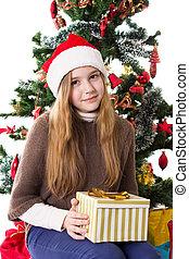 Teenage girl in Santa hat with present under Christmas tree