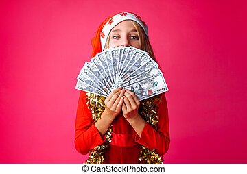 teenage girl, in Santa's hat and with tinsel on her neck, with dollars in her hands , isolated on a red background.