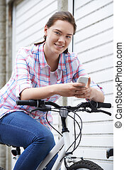 Teenage Girl In Urban Setting Using Mobile Phone Whilst Riding Bike