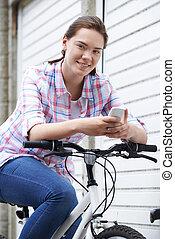Teenage Girl In Urban Setting Using Mobile Phone Whilst Riding Bike