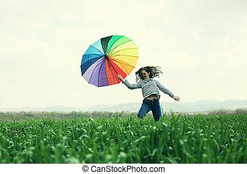 Teenage girl jumping in the green field