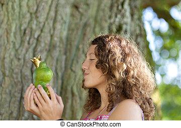 Teenage Girl Kissing Toy Frog Against Tree Trunk
