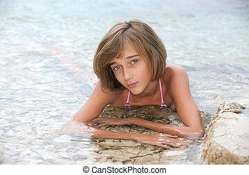 Teenage girl laying in the sea water