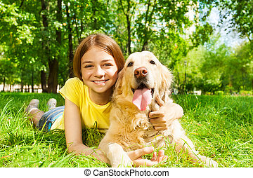 Teenage girl laying with her pet dog in park
