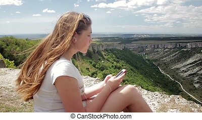 Teenage girl listening to music with headphones on smartphone on a background of mountains