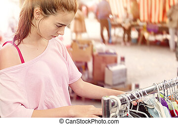 teenage girl looking for clothes at a flea market