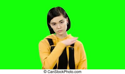 Teenage girl looks forward angrily. Green screen - Teenage...