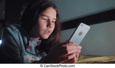 Teenage girl looks on her smartphone in bed during the...