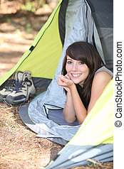 Teenage girl lying down in tent